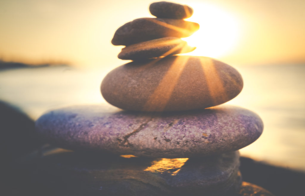 Balance of rocks stacked on one another with a sunset shining through and with a body of water in the background. Relating to the importance of balance when decision-making.